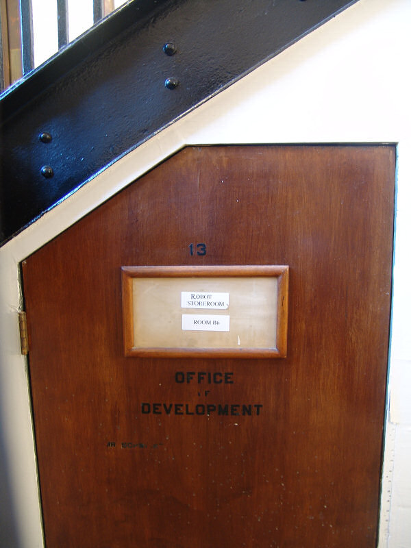 "A door, labelled as the ""Office of Development"" as well as the ""Robot Storeroom"""