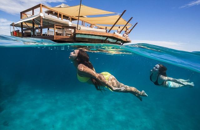 Плавающий в Тихом океане у побережья Фиджи, роскошный двухэтажный остров предлагает коктейли, еду и бесконечные вид океана