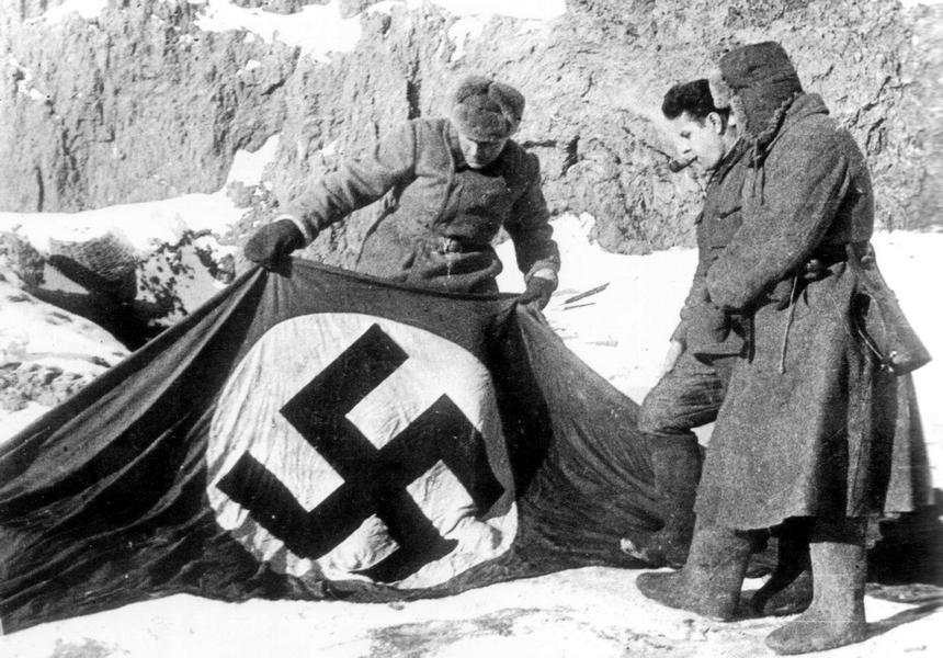 Советские бойцы рассматривают захваченный нацистский флаг на берегу Волги в Сталинграде.