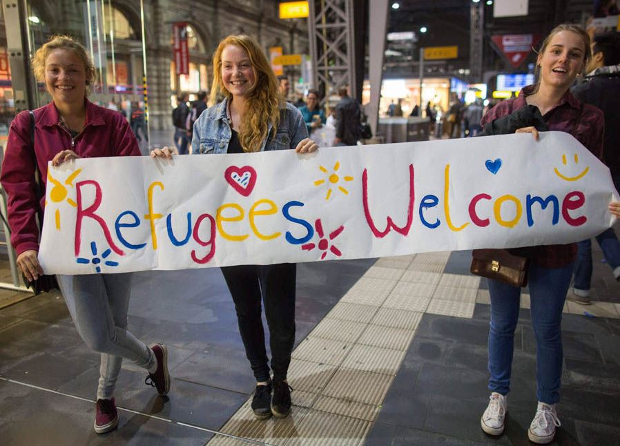 Girls-standing-with-sign-welcoming-migrants-70132.jpg
