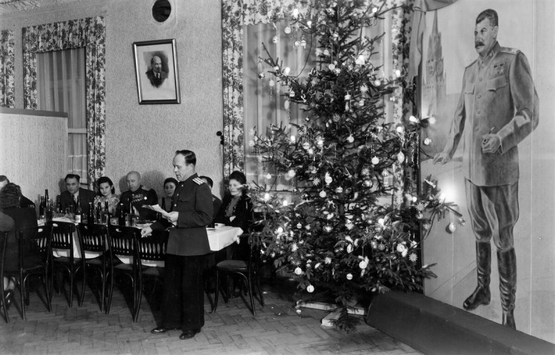 Новый год в послевоенной сталинской Совдепии - какой-то партиец-упырь зачитывает доклад о новых достижениях Партии и Правительства во главе с любимым вождем Джугашвили. Вождь сурово, с видом грузинского уголовника, взирает на совков и на то, как они празднуют Новый год, с большого портрета справа.
