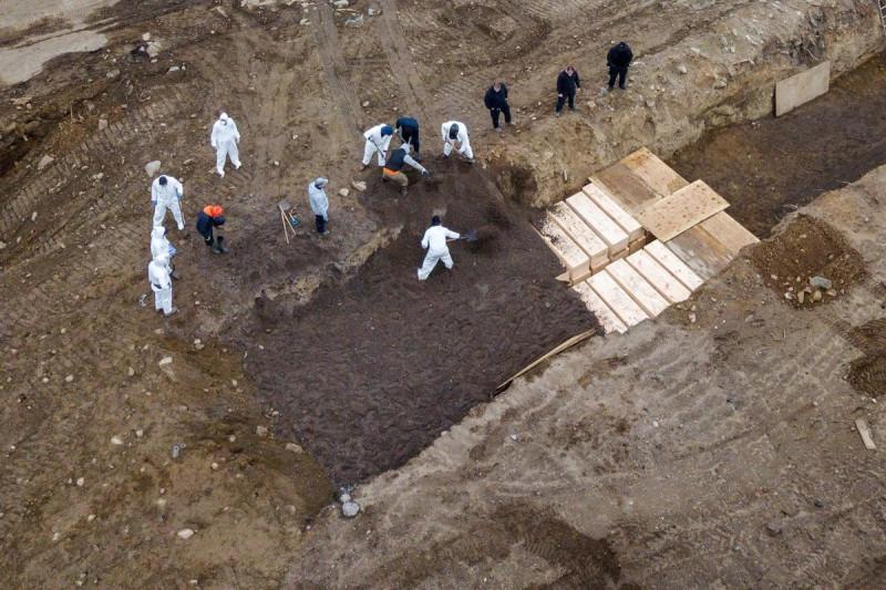 """Тупые пиндосы из похоронной команды укладывают и засыпают гробы с умершими от """"американки"""" в два ряда и несколько слоев в огромные траншеи на острове Харт в Нью-Йорке."""