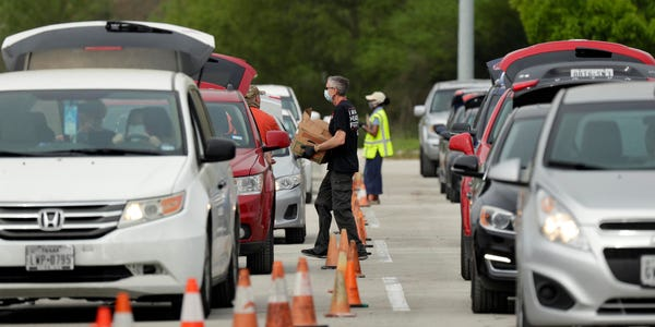 Довольный тупой пиндос тащит бесплатный набор еды к своей машине.
