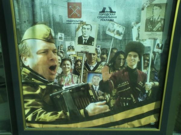 """Плакат ко """"дню победы"""" в Петербурге: осовеченный Ваня-дурачок, изображающий """"вытирана"""", играет на гармошке какому-то начальству и Неруси. Давай-давай, Ваня, играй! Спляши еще перед ними! Тебе ведь есть что праздновать — на этой войне твоему русскому народу большевики, считай, позвоночник переломили. Ах, как хорошо! Какой великий праздник!"""