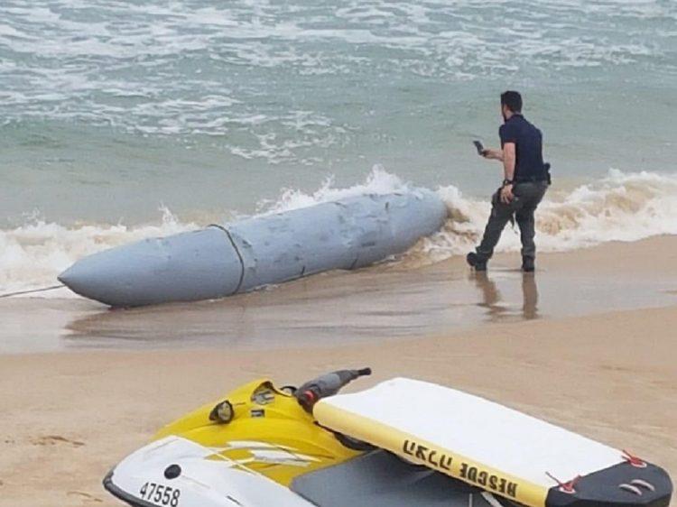 Смелый сраильский полицай аккуратно обследует и фотографирует загадочный предмет, найденный на побережье Сраиля. А вдруг там деньги? Или, наоборот, бомба?