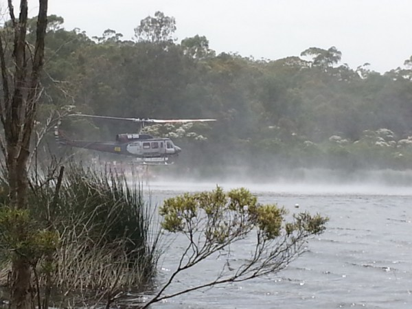 Fire Service helicopter hovering over water, kicking up spray