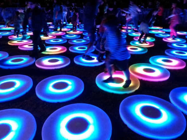 People, mostly children, jumping across lit up circles with changing colours