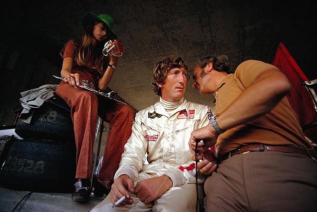1970, Гп Австрии. Глава команды Lotus Колин Чэпмен и Йохен Риндт на пит-лейн. Рядом – жена гонщика Нина. Через 3 недели Риндт погибнет в результате аварии в Монце