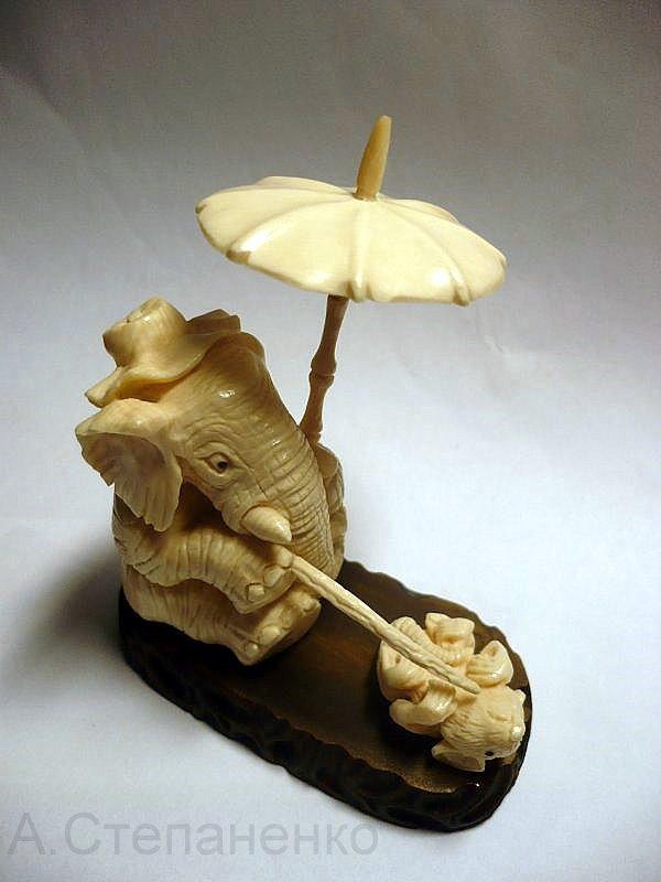 Слон в шляпе и с зонтиком, играющий с мышкой.