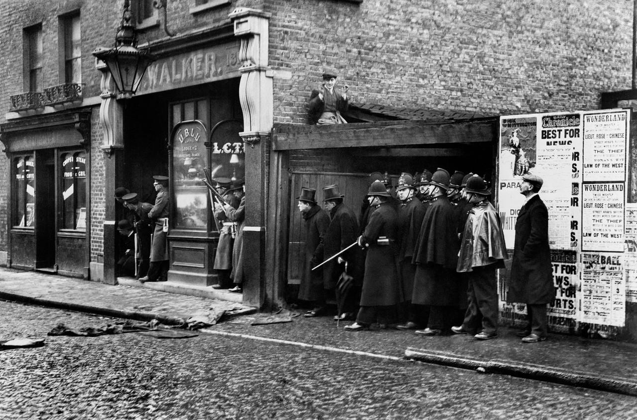 1911. Министр внутренних дел Уинстон Черчилль (слева в цилиндре) во время осады  латышской анархистской группировки на Сидней-стрит в Степни, Восточный Лондон. 3 января