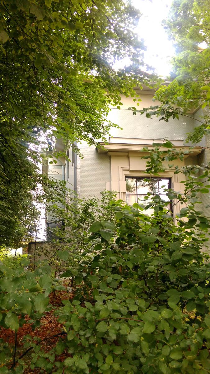 Территория очень зеленая. Листва с некоторых ракурсов почти полностью скрывает здание..