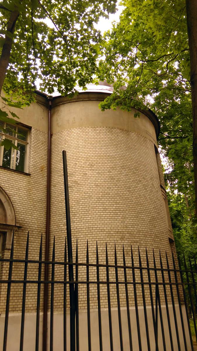 Угловая круглая башня и острые пики ограды..