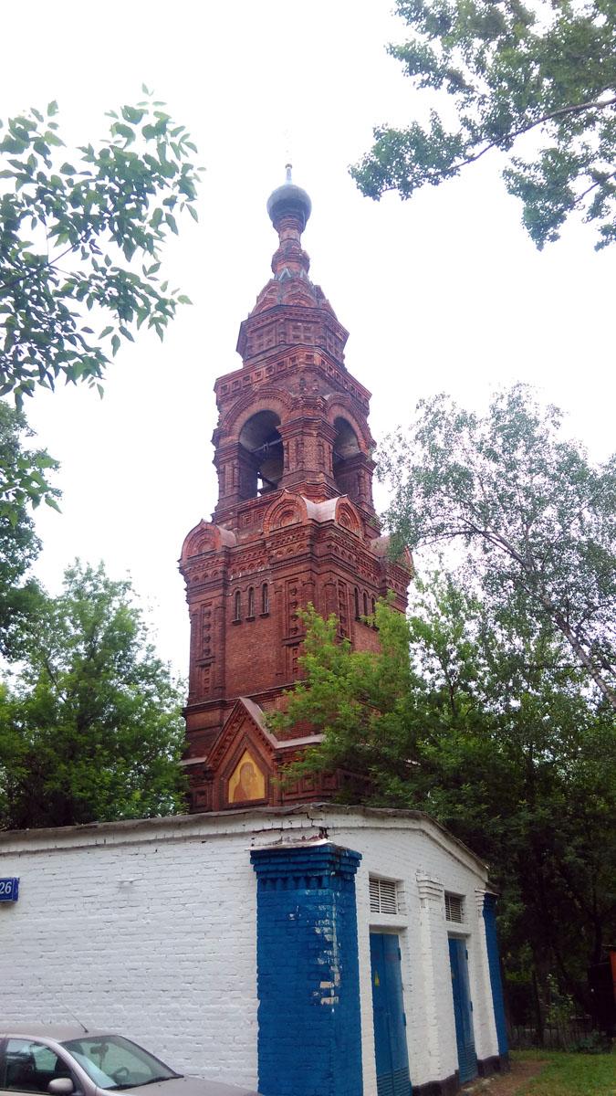 Во дворе обычных многоэтажек, среди деревьев высится одинокая колокольня. Одинокая потому, что церкви или других религиозных сооружений во дворе нет. Не считать же таковым небольшую церковную лавку расположенную рядом.