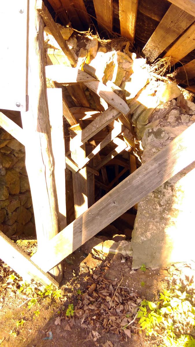 Своды погреба укреплены деревянными опорами, сверху сделаны временные навесы от осадков, которые уже и сами частично разрушены.