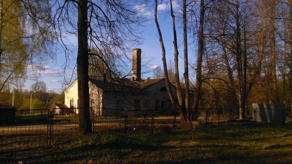 За забором напротив церкви здание бывшей поселковой бани. На высокой трубе гнездо аистов.