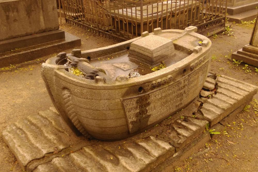 Надгробие купца Симона Дмитриева (1729-1799). Перенесено с Большеохотинского кладбища. Гранитная барка со снастью и якорями с крестообразными стволами, помещенная на постамент в виде волн. Неизвестный мастер конца XVIII.