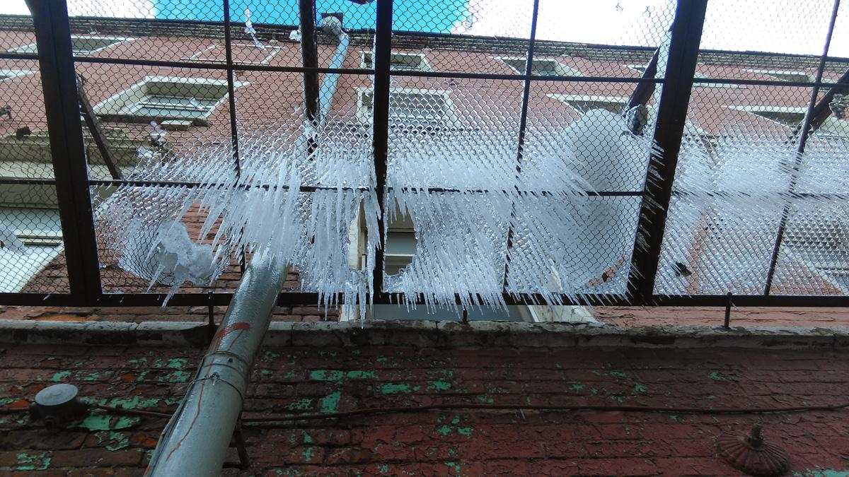 Зима притаилась на защитной сетке на здании общежития бывшего завода «Красный суконщик» 1870 года постройки.