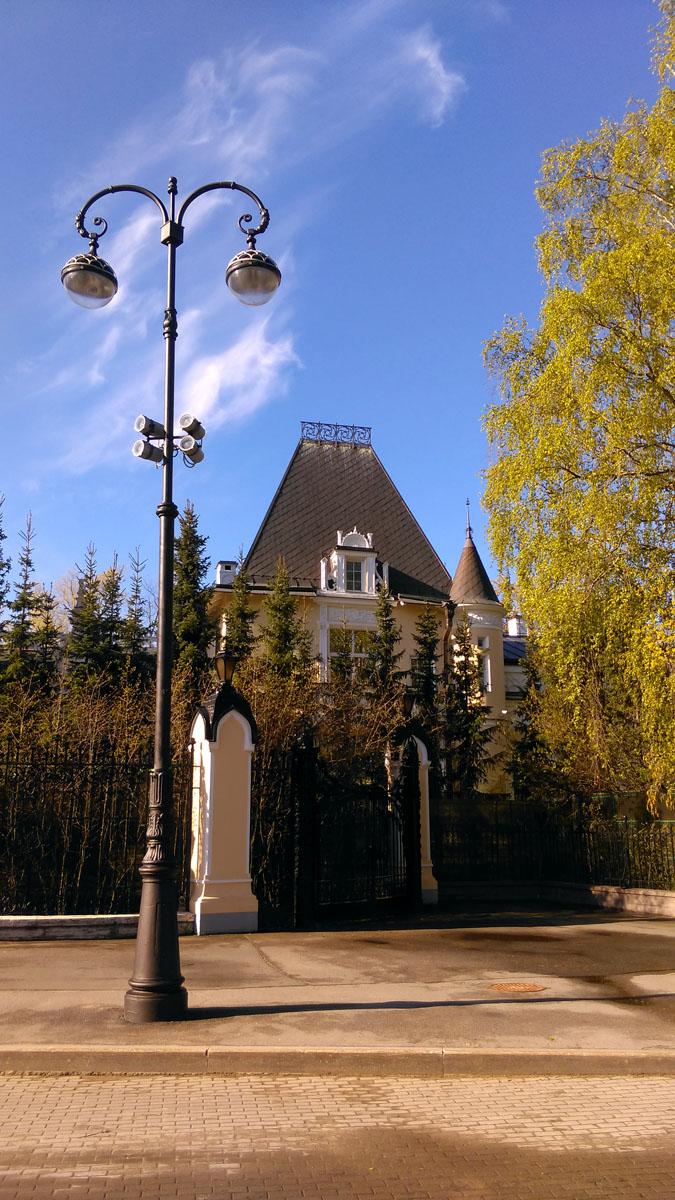 Вид на здание перекрывает забор и плотно посаженные елки.