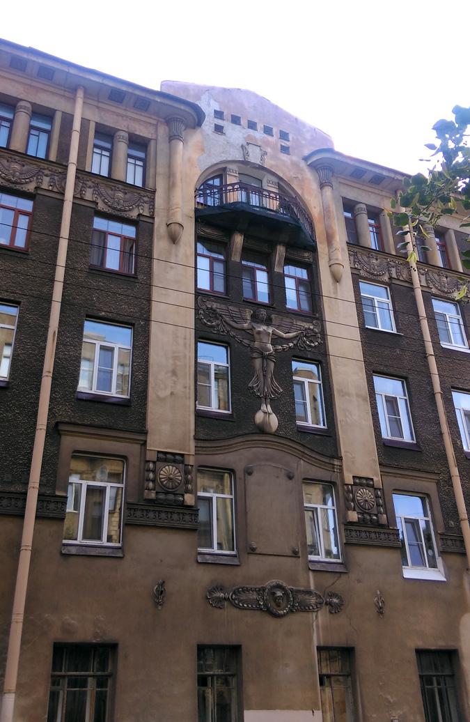 Но центральной фигурой декора фасада, конечно, является гений славы в облике прекрасной юной девушки, стоящей на шаре и держащей в руках гирлянду из лавровых листьев