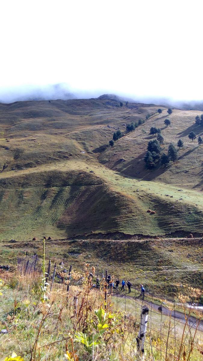 Вершина горы Итколбаши тоже закрыта облаками. По ее подножию идет группа туристов.