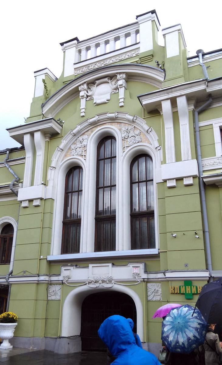 Арка ворот во двор, красивое тройное витражное окно и растительный орнамент на фоне плитки. А раньше на этом месте была решетка между главным зданием и флигелем.