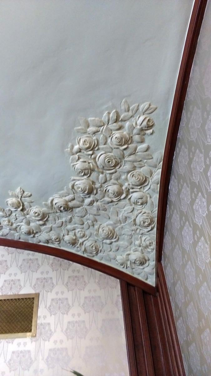 Лепнина в виде роз на потолке, шелковые обои и решетка вентиляции.