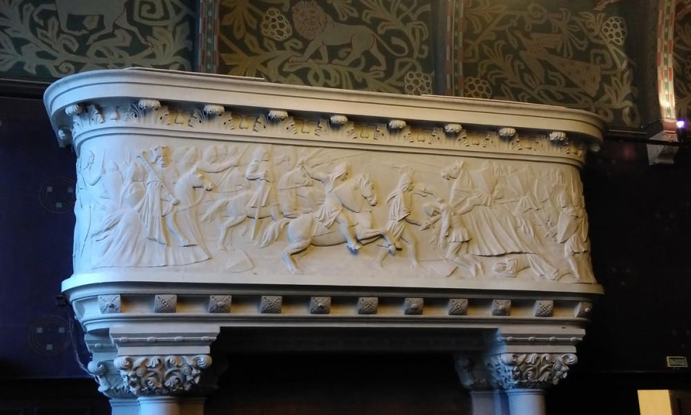 Большой камин с гипсовым барельефом средневековой битвой.