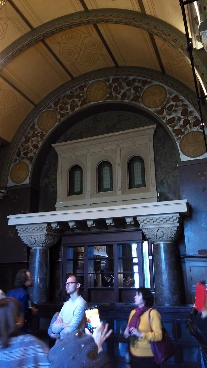 Массивные колонны, три ложных окна в резных наличниках. Такое ощущение, что это вход в какое-то другое, не менее грандиозное помещение...