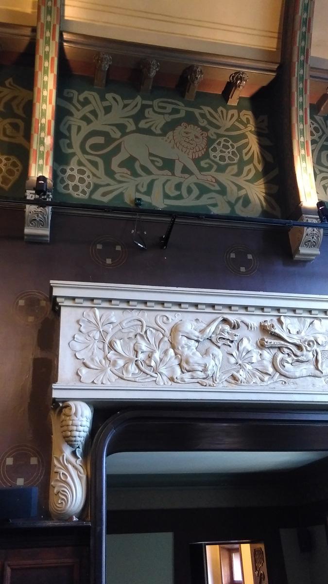 Над аркой барельеф, изображающий схватку дракона и собаки.