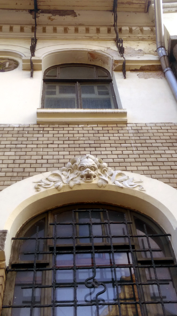 Химера, притаившаяся в цветах на арке окна.
