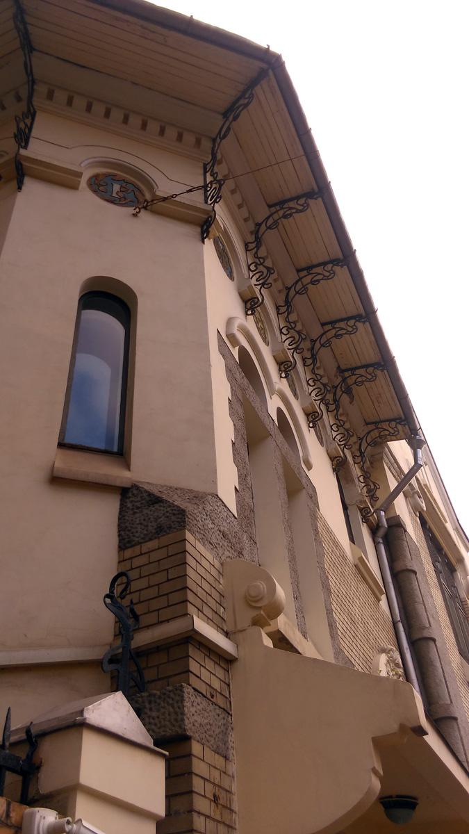 Карнизы крыши вынесены далеко вперед над стенами, их поддерживают фигурные кованые кронштейны.
