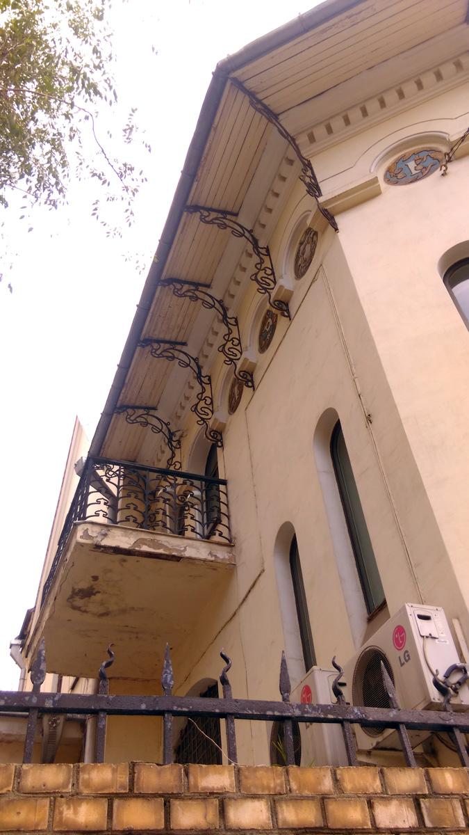 Через ограду фотографируем внутренний фасад с балконом и кондиционерами.