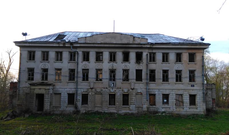 Большинство окон и дверей либо пустые, либо заколочены. Балкон давно упал.