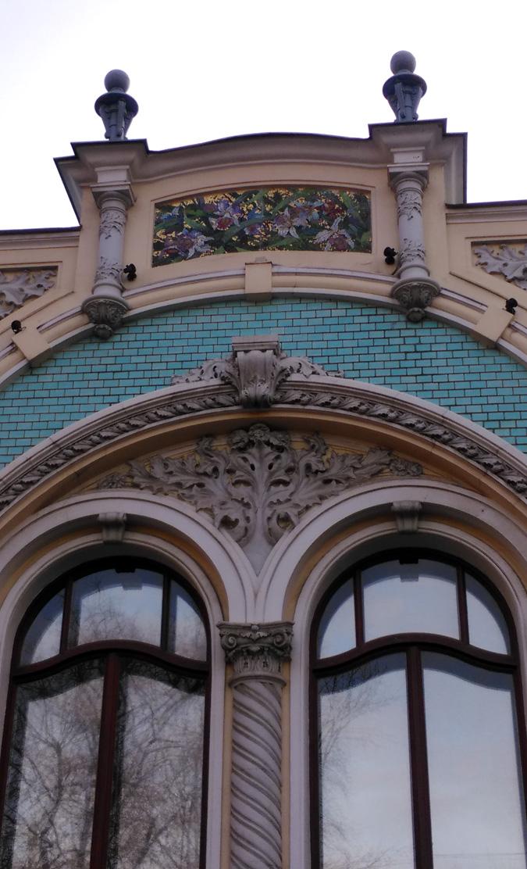 Над этим окном на аттике помещено мозаичное панно, где на золотом фоне изображены орхидеи или ирисы.