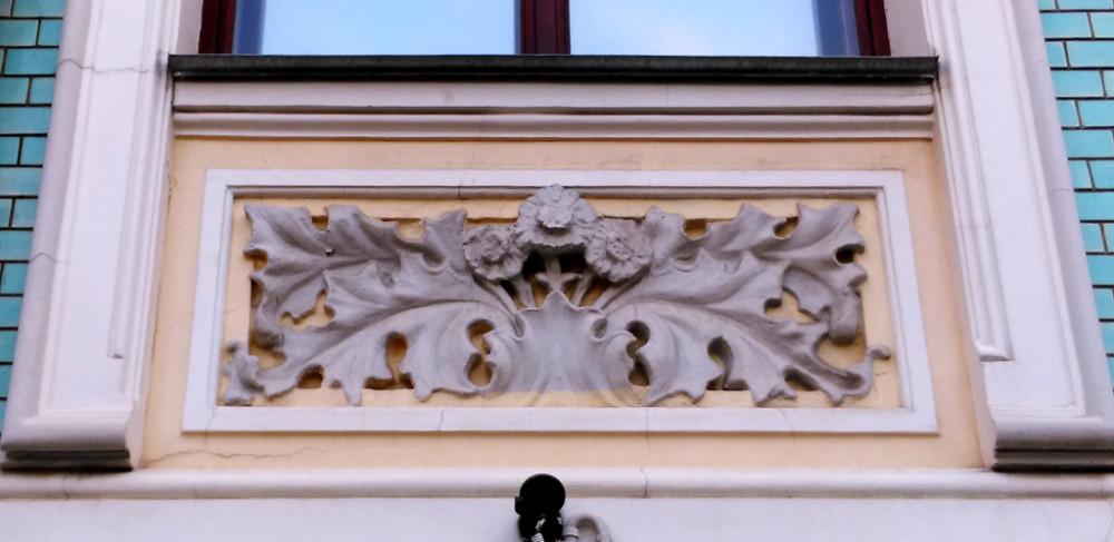 Под окнами каменные цветы и листья. Скорее всего это герберы, чьи листья похожи на листья коринфского чертополоха.