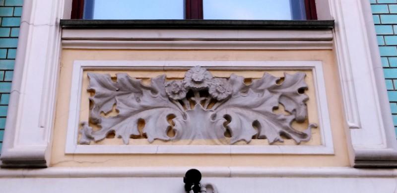 Под окнами каменные цветы и листья. Скорее всего, это герберы, чьи листья похожи на листья коринфского чертополоха.