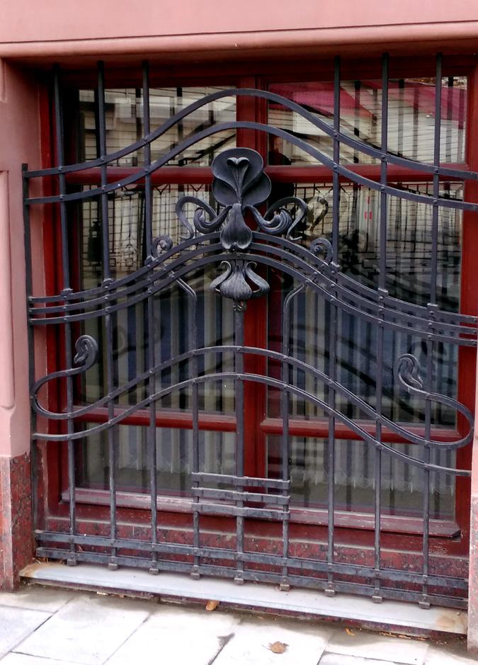 Окна полуподвального этажа закрыты коваными решётками с цветами ириса или орхидеи.