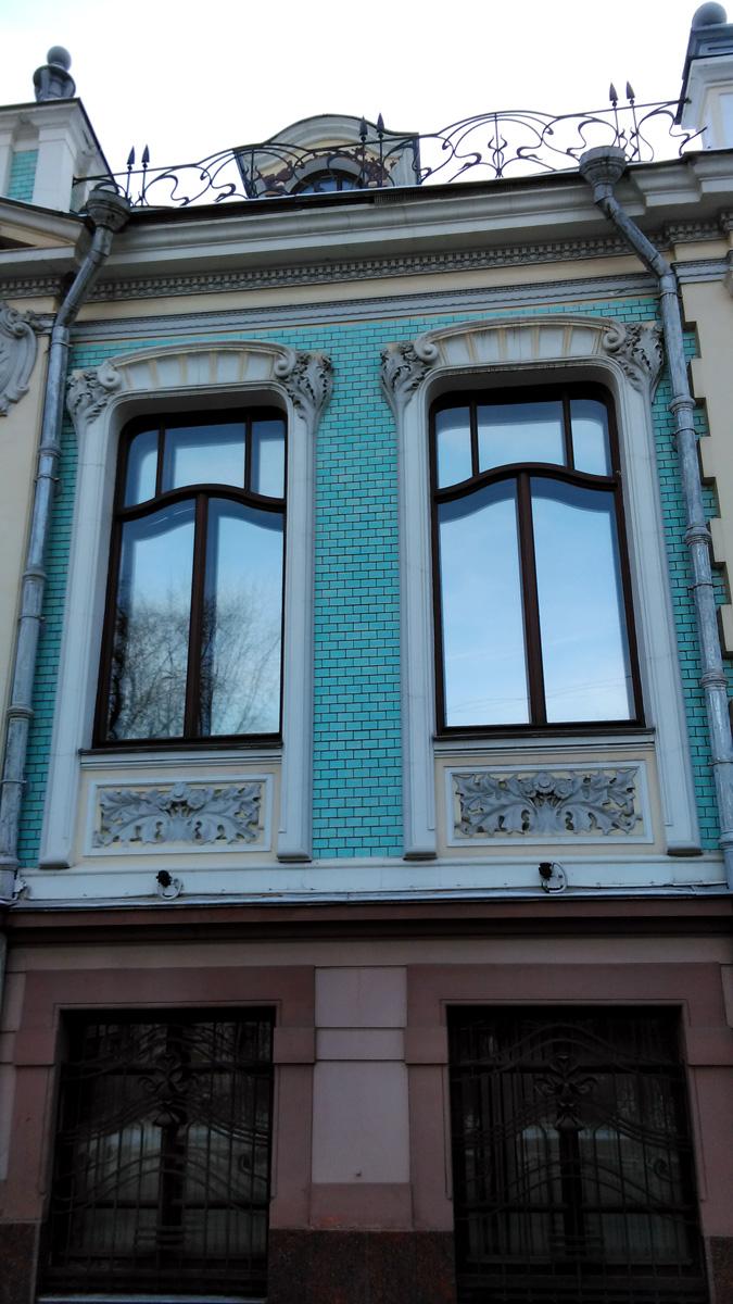 Часть фасада покрыто бирюзовой глазурованной плиткой. Облик дома дополнен коваными ажурными решетками парапета на крыше здания.