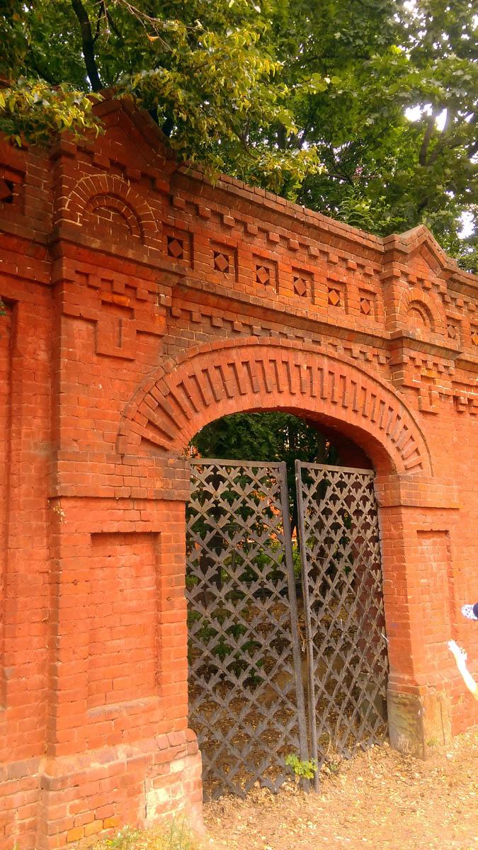 Закрытые решётчатые ворота в стене и уже вросшие в землю.