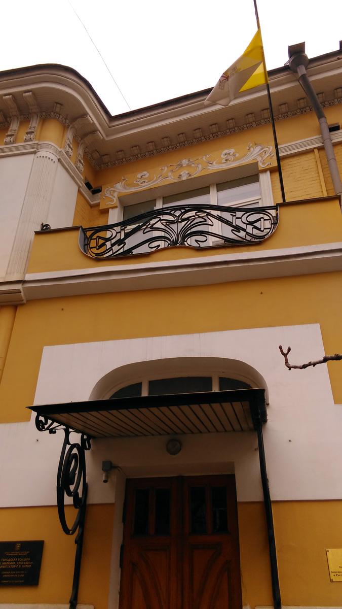 Над дверью балкон с красивой железной решеткой.