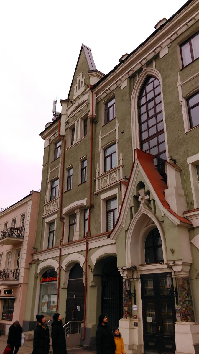Четырехэтажный кирпичный дом, построенный архитектором С.М. Гончаровым в 1905 году в стиле модерн с готической стилизацией на фасаде. Прохожие любуются творением архитектора.