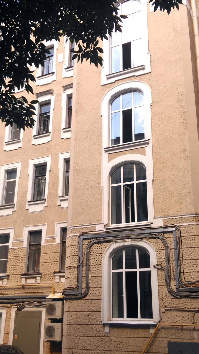 Мы привыкли, что дворы в Ленинграде больше напоминают колодцы, но у этого дома вполне просторный двор. Точнее, два внутренних двора со сквериками и даже с большими деревьями, а также с большими окнами мастерских наверху, скромной, но стильной отделкой, выполненной в разнофактурной штукатурке с крупными геометрическими узорами.
