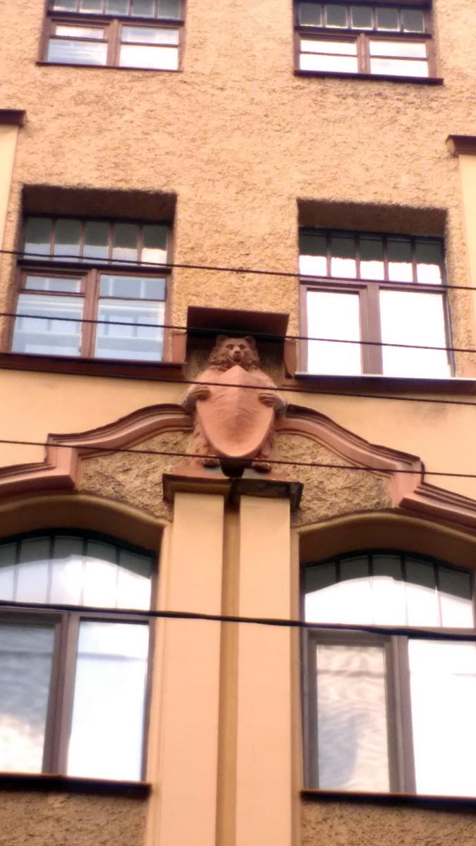 Встав на дыбы, медведи,  зажатые деталями рассчитанного на два окна наличника барочных очертаний,  передними лапами удерживают щиты.