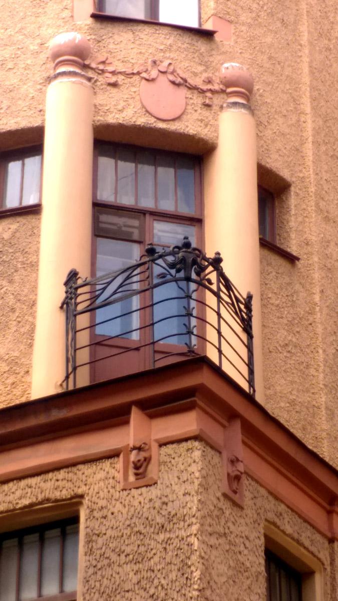 Треугольный балкон, а под ним маски также вписанные в треугольный объем.