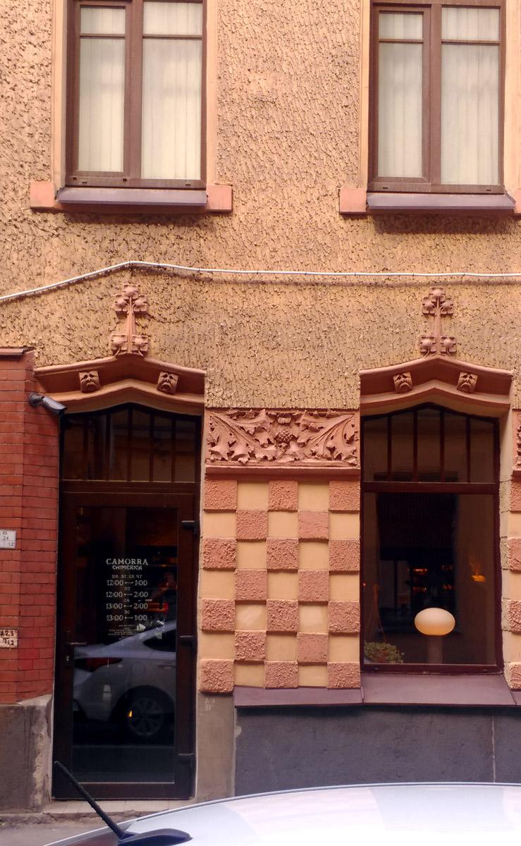 Над окнами и дверьми кубические плаксивые маски и  подобия готических  крестоцветов. А в промежутках между окон чертополох над шахматным полем.