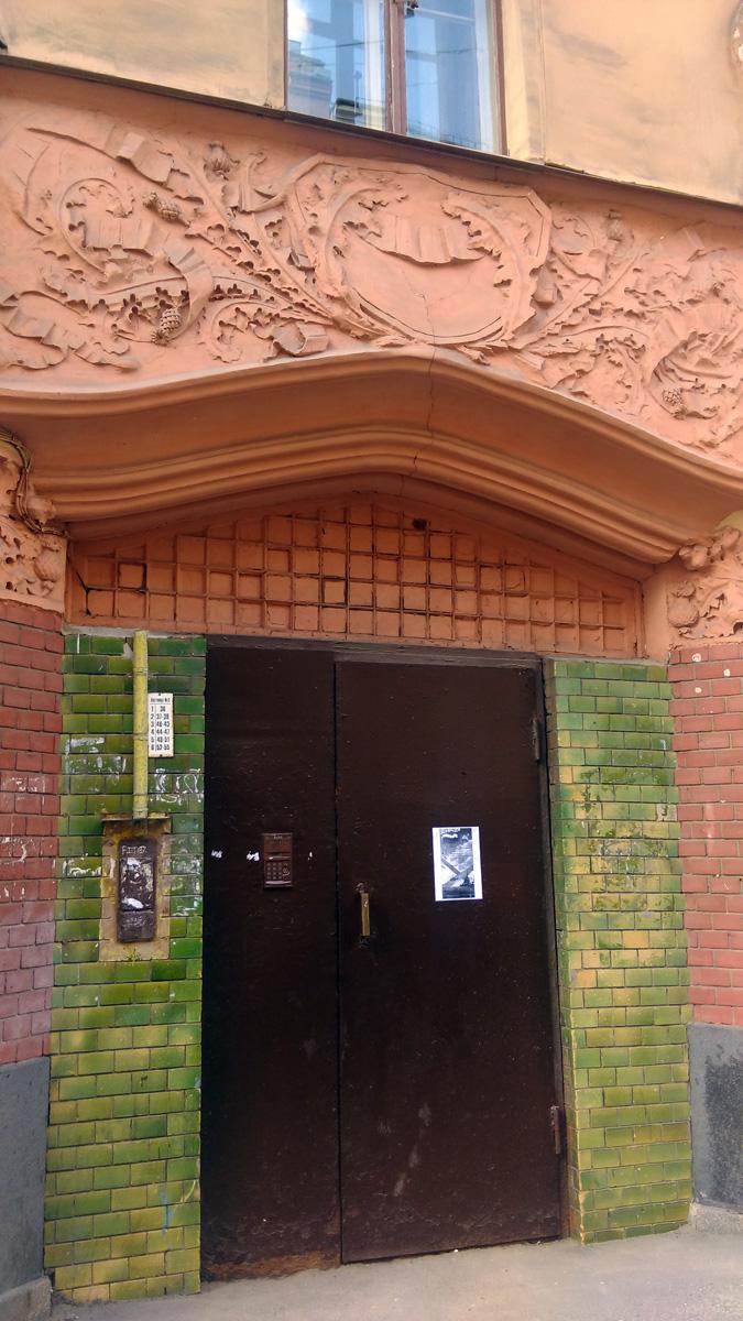 Чертополох и зеленая плитка обрамляют входную дверь, которая к сожалению заменена на железную. Над дверью, полагаю, было широкое окно в клеточной расстекловке, ныне закрашенное или замазанное.