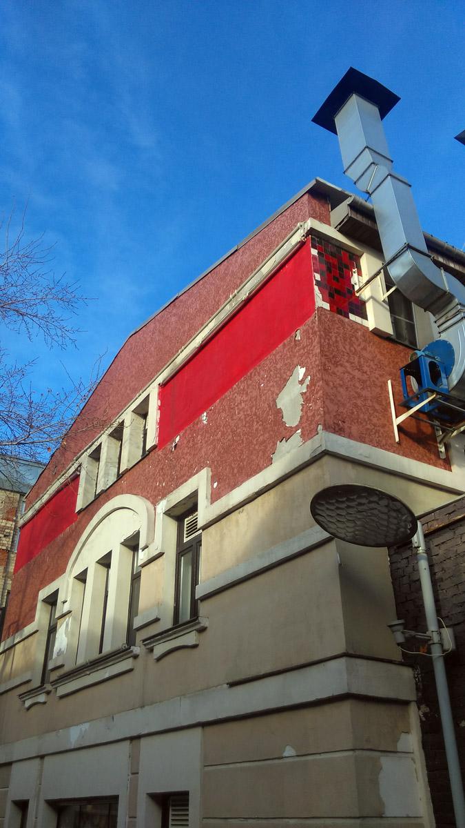 Плитка на главном фасаде и слева уже то ли отвалилась, то ли с нее осыпалась эмаль. Теперь здесь просто краской накрасили красную полосу. Да и остальная штукатурка сыпется...
