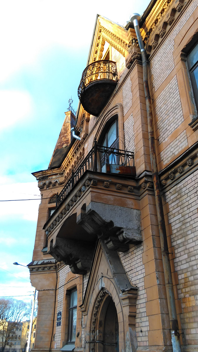 Массивный солидный балкон с ажурной оградой, а над ним маленький, почти игрушечный легкий полукруглый балкончик.