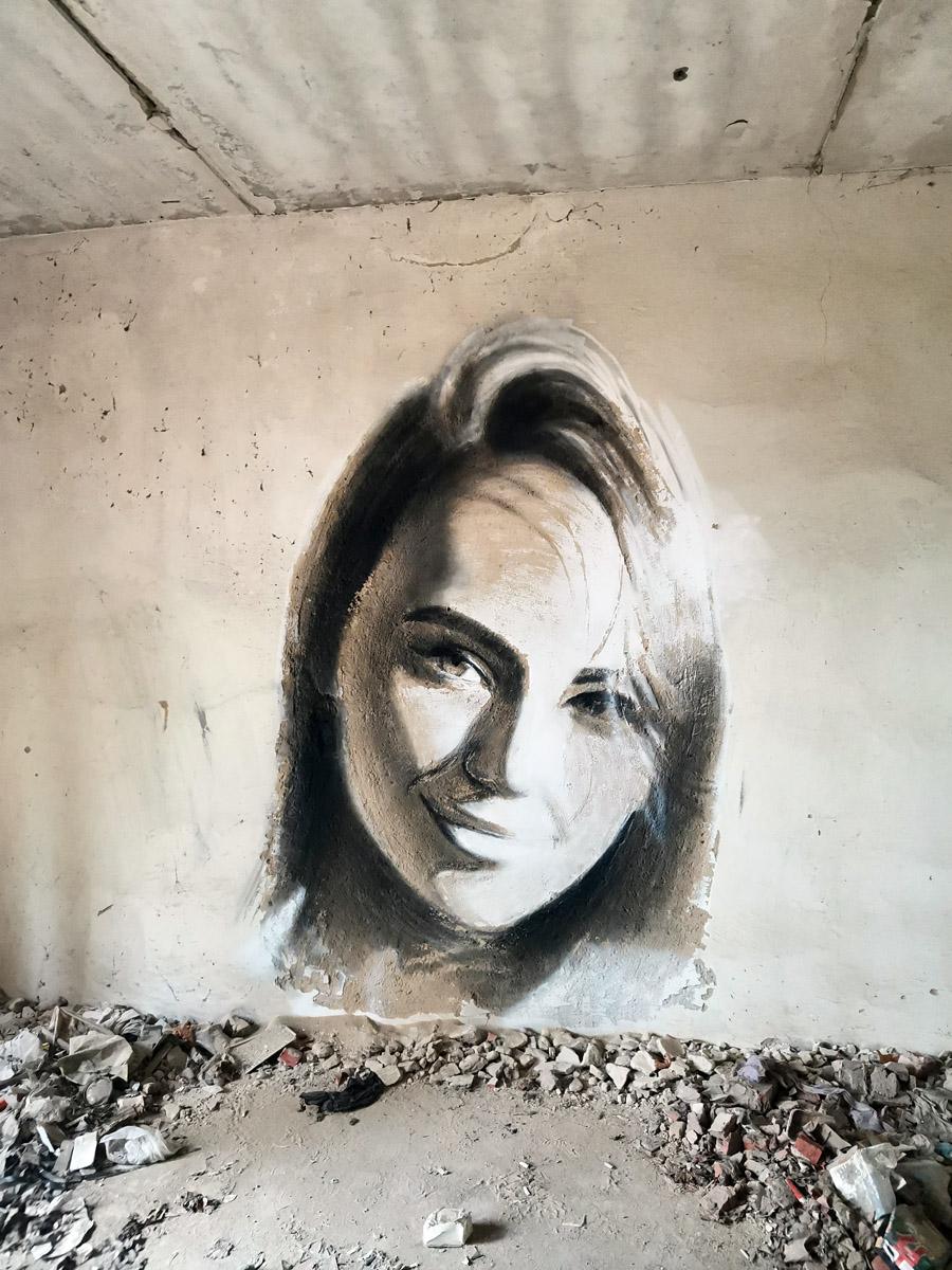 Внутри здания на стенах портреты девушек, выполненные в интересной технике.