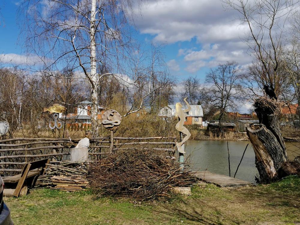 Местные умельцы украшают причудливыми поделками из дерева берега пруда и свои постройки. Кстати, справа на пеньке черный ворон тоже деревянный.